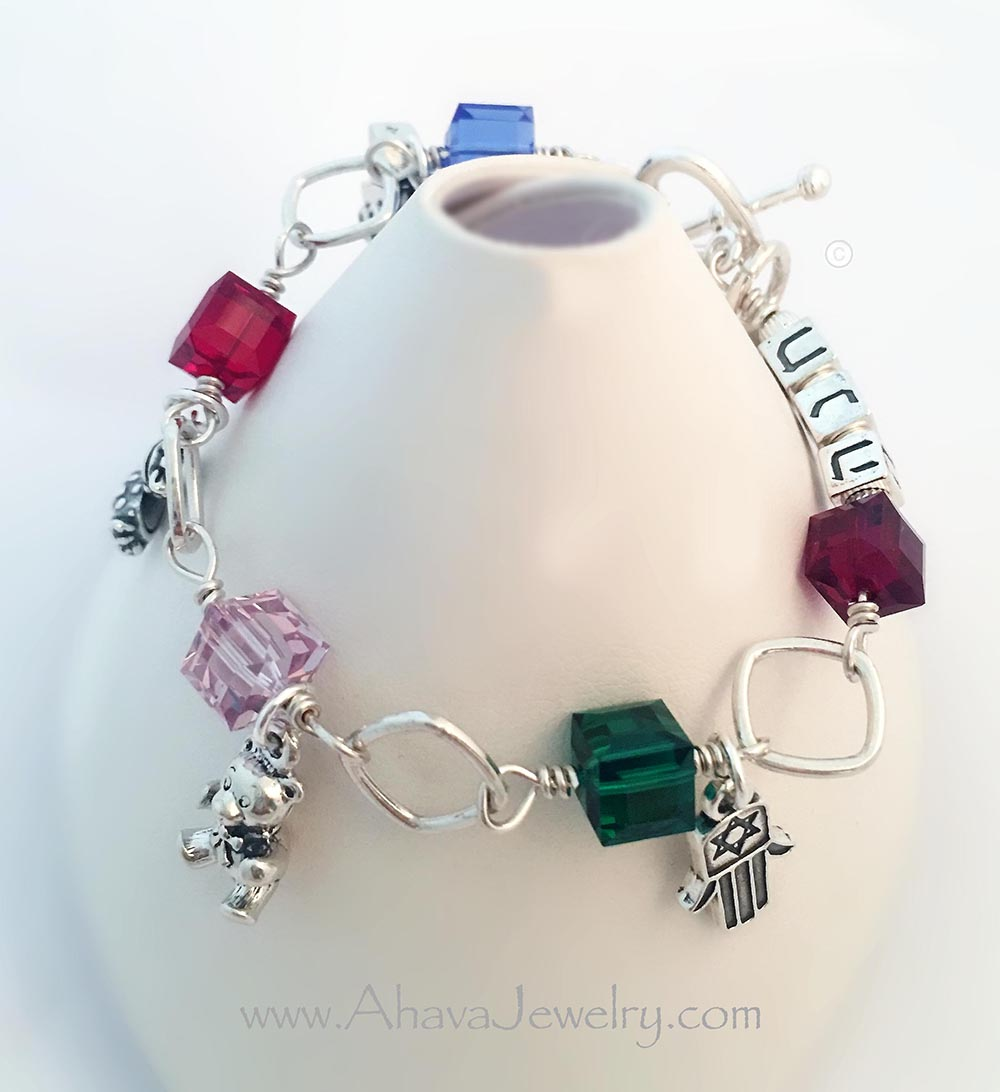 This Safta or Savta Birthstone Bracelet is shown with 5 Birthstones by Swarovski and 5 Sterling Silver Charms (Baby Carriage Charm, Baby Girl Booties Charm, Teddy Bear Charm, Hamsa Hand Charm and a Heart Charm with SAFTA hand-stamped). They picked the Heart Toggle Clasp. The Birthstones are September or Sapphire, July or Ruby, June or Light Amethyst, May or Emerald and February or Amethyst. They also added Foundness in Hebrew block letters: חבה
